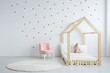 Pastel pink armchair next to wooden house shape bed with toy and blanket, copy space and golden stars on empty white wall, round white carpet on floor