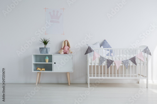White wooden crib with pillows next to wooden cabinet with toy and green pant in grey, copy space on empty white wall