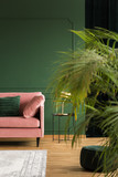 Vertical view of elegant green living room with patel pink couch, coffee table and copy space on empty wall