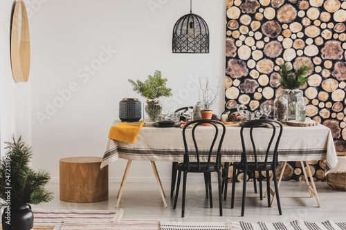 Forest inspired dining room with wooden wallpaper and stylish black chandelier - 247231871