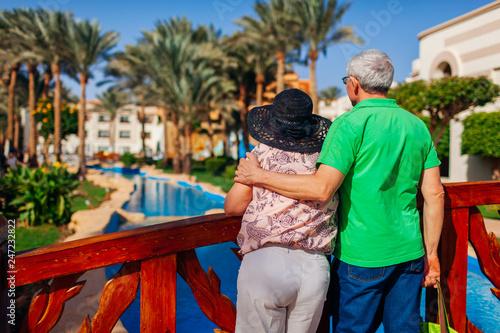 Leinwandbild Motiv Senior couple relaxing by swimming pool on hotel territory. People enjoying vacation. Valentine's day