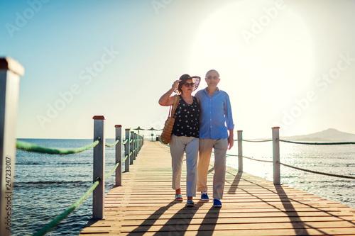 Leinwanddruck Bild Senior couple walking on pier by Red sea. People enjoying vacation. Valentine's day
