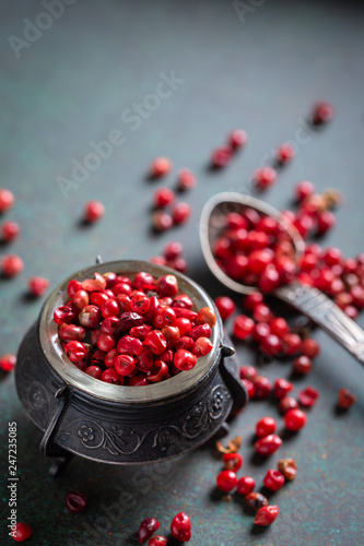 Pink pepper in vintage bowl on dark background. Closeup, selective focus - 247235085