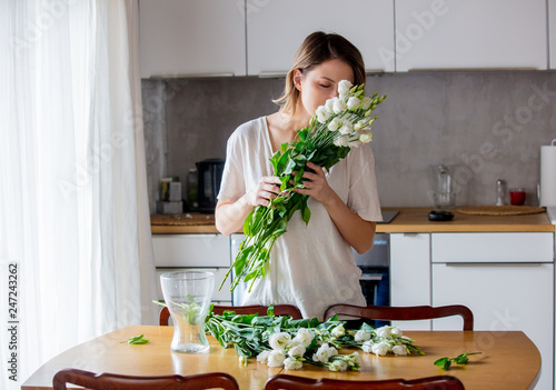 Leinwandbild Motiv a girl in a white T-shirt is preparing a bouquet of white roses before putting them in a vase on the kitchen table. Lifestyle concept