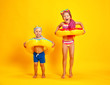 Leinwandbild Motiv happy children girl and boy in swimsuit with swimming ring donut on colored yellow background.