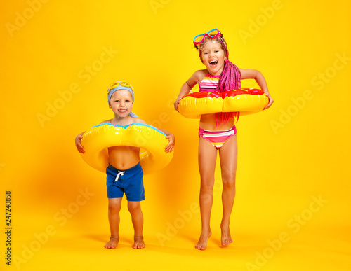 Leinwanddruck Bild happy children girl and boy in swimsuit with swimming ring donut on colored yellow background.