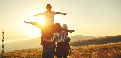 Happy family: mother, father, children son and daughter on sunset.