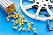 Cinema concept. film stock and popcorn on blue background - 247277275