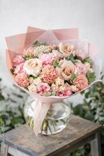 beautiful fresh cut bouquet of mixed flowers in vase on wooden table. The work of the florist at a flower shop. Delicate Pastel tones color