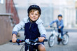 Leinwandbild Motiv Two school kid boys in safety helmet riding with bike in the city with backpacks. Happy children in colorful clothes biking on bicycles on way to school. Safe way for kids outdoors to school