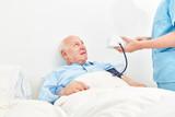 Pflegekraft misst den Blutdruck eines alten Mannes als Patient im Krankenhaus