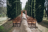 on the cypress avenue in Tuscany there is an arch for the wedding ceremony, which is decorated with floral compositions and a pink cloth, nearby are chairs for guests - 247307029