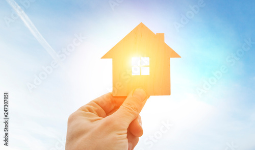 Man's hand holds wooden flat house against the sun