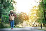 Asian woman backpack on the road and forest background, journey and traveling on holiday concept . - 247309007