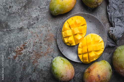 Fresh mango tropical fruits over gray background, top view with Copy space. - 247310261