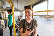 Beautiful smiling Caucasian girl with brown hair and sunglasses on head standing in city bus and using smart phone.