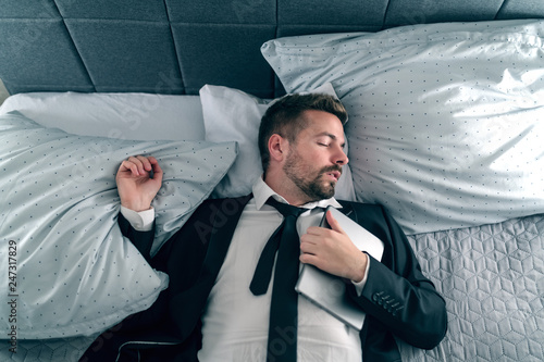 Leinwanddruck Bild Overworked businessman in suit sleeping and lying on the bed and holding tablet on his chest.