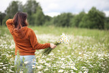 Beautiful girl collects daisies in summer field - 247326082