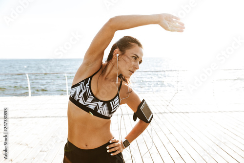Leinwandbild Motiv Beautiful young sports fitness woman make stretching exercises at the beach outdoors listening music with earphones.