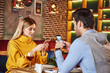 Leinwanddruck Bild - Always with smartphone. Young couple are sitting in restaurant with smartphones