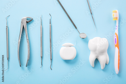 fototapeta na ścianę Dental health and teethcare concept. Professional steel dental instruments with a mirror near white tooth model, toothbrush and dental floss on light blue background.