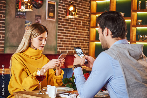 Leinwandbild Motiv Always with smartphone. Young couple are sitting in restaurant with smartphones