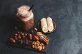 Chocolate smoothie in a jar, protein milkshake, nuts, chocolate cubes, banana slices, dates, cinnamon sticks, healthy eating on a dark background