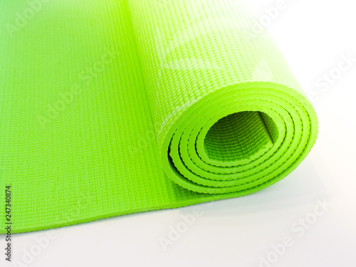 Woman rolling her Yoga mat after a workout - top view.Healthy life, keep fit concepts.Equipment for yoga. Top view green  yoga mat sport isolated.Rolled up yoga mat isolated on white. Copyspace.  - 247340874