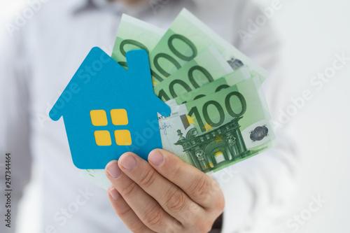 Leinwanddruck Bild haus in hand mit geld