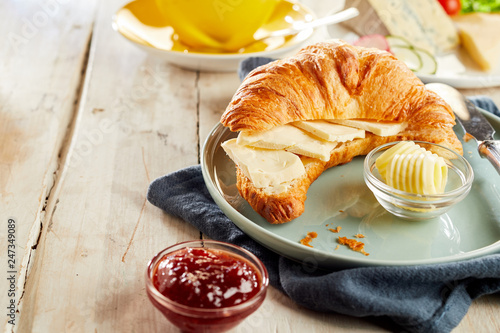 Leinwandbild Motiv Croissant sliced in half, served with cheese