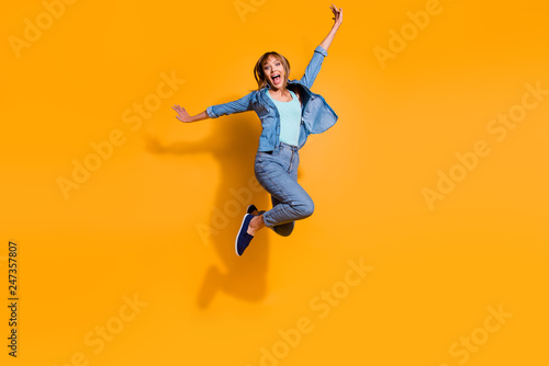 Leinwandbild Motiv Full length body size photo jumping flight high amazing beautiful she her lady hands arms legs in win  raised up glad yell wearing casual jeans denim shirt clothes isolated on yellow background
