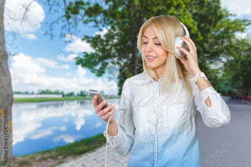 Happy young blonde woman listening to music - 247360609