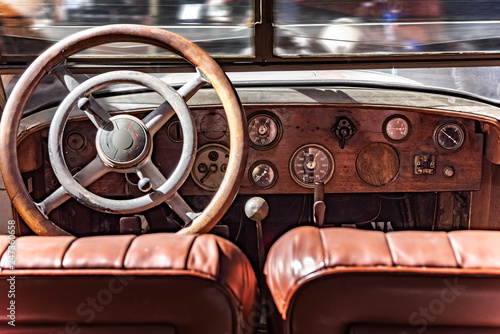 Leinwandbild Motiv Cabin from inside a retro car. Wooden dashboard and steering wheel.