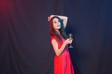 Party, holidays and celebrations concept - Cheerful charming young woman in red dress drinking champagne or wine and dancing over dark background