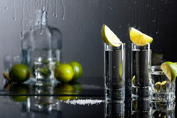 Glasses of tequila with lime and salt on the black reflective background.