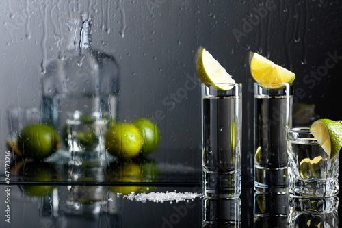 Leinwanddruck Bild Glasses of tequila with lime and salt on the black reflective background.
