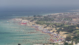 Aerial view of beautiful beach with hundreds of people having bath