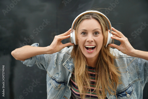 Dynamic young student listening to music with headphones on black background