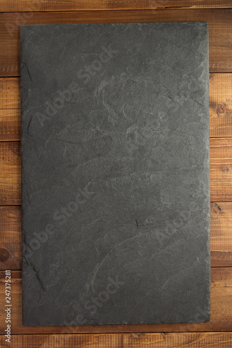 slate stone at wooden background - 247375281