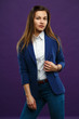 Portrait of a young girl in business suit isolated on a purple background.