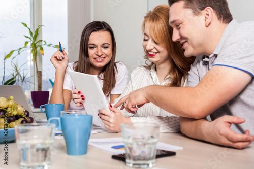 fototapeta na ścianę geschäftsleute diskutieren über ein produkt während sie mit einem tablett computer arbeiten. zwei kauffrauen und ein kaufmann während einer beratung