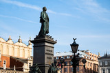 Sunshine view of bronze monuments on marble pedestal and ancient towers architecture on the Krakow city central square
