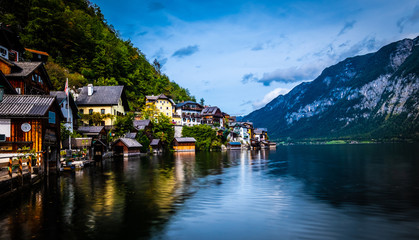 Evening scenery of lake and wooden buildings at the berth on the background of mountains in Hallstatt, Austria
