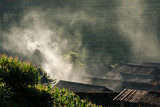Rooftops and smoke in rice terraces landscape China