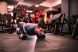 Muscular man doing push-up exercise with dumbbell, cross fit workout.