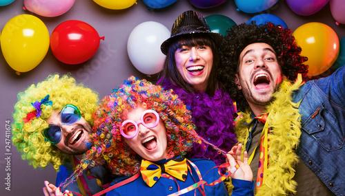 Leinwanddruck Bild Karneval Party,Lachende Freunde in bunten Kostümen feiern Karneval .