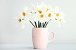 White narcissus flowers in mug on grey background