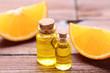 Leinwanddruck Bild - Orange oil in bottles on brown wooden table
