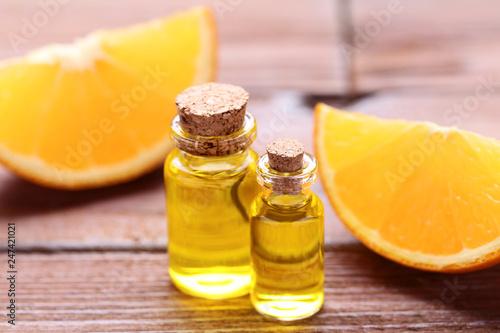Leinwandbild Motiv Orange oil in bottles on brown wooden table
