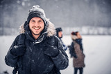 Portrait of a happy hiker guy with a backpack walking with his friends through a winter woods - 247428435